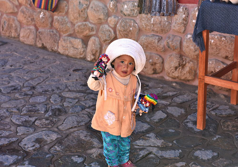 Little girl in Chincheros Peru Llama Travel